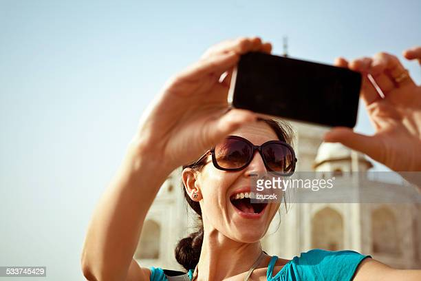 Young woman taking selfie with Taj Mahal