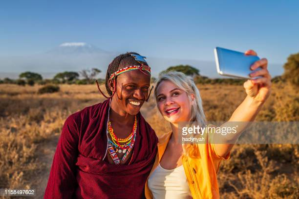 young woman taking selfie with warrior maasai, mount kilimanjaro on background, kenya, africa - shield volcano stock pictures, royalty-free photos & images