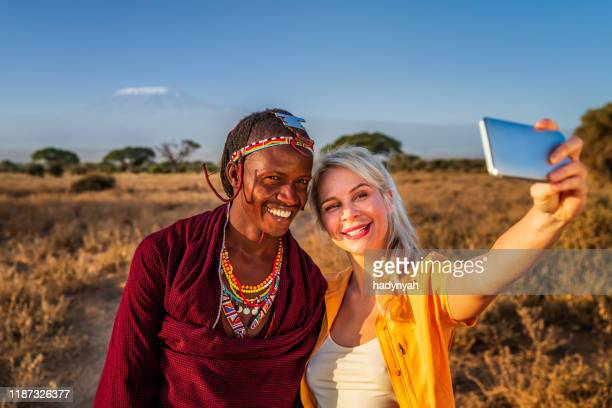 young woman taking selfie with warrior maasai, mount kilimanjaro on background, kenya, africa - east african tribe stock pictures, royalty-free photos & images