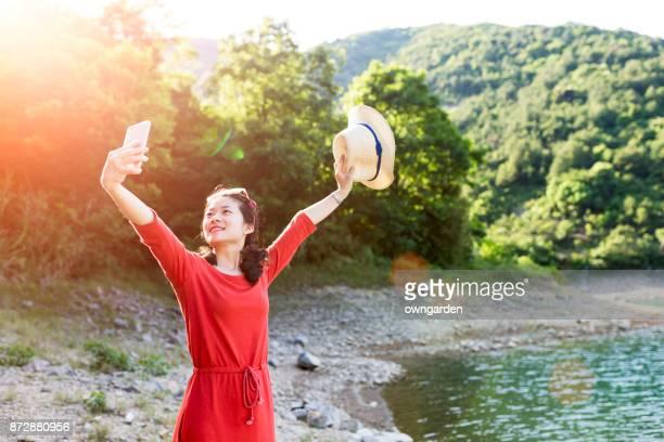 Jeune femme prenant selfies avec son téléphone Mobile