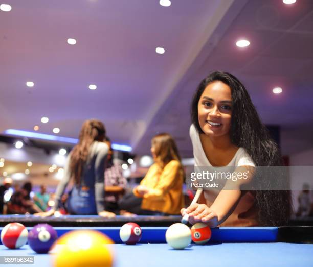 Young woman taking shot on pool table