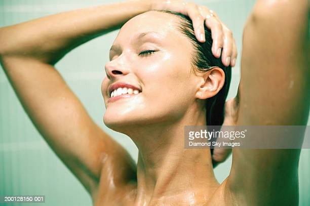 Young woman taking shower, hands on head, smiling, close-up