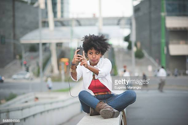 Young woman taking smartphone selfie whilst sitting on shopping center wall