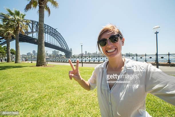 Young woman tales selfie portrait with Sydney harbour bridge