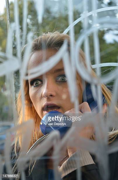 young woman talking in a graffiti'd phone box - depczyk stock pictures, royalty-free photos & images