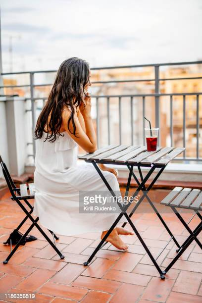 young woman talking on a cell phone sitting outside on a balcony - long dress stock pictures, royalty-free photos & images
