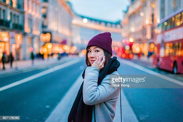 Young woman talking on cell phone in city