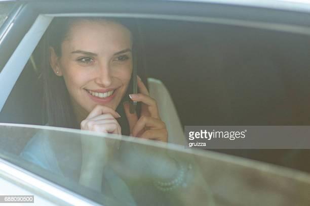 Ung kvinna talar i mobiltelefon i baksätet av en bil