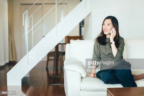 young woman talking on cell phone on the sofa in living room - rispondere foto e immagini stock
