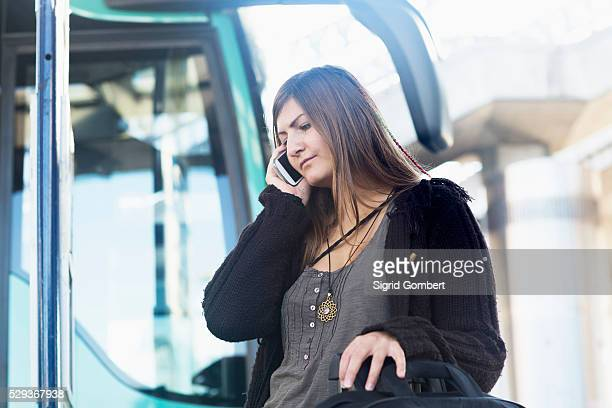 young woman talking on mobile phone and standing in front of bus, freiburg im breisgau, baden-w��rttemberg, germany - sigrid gombert 個照片及圖片檔