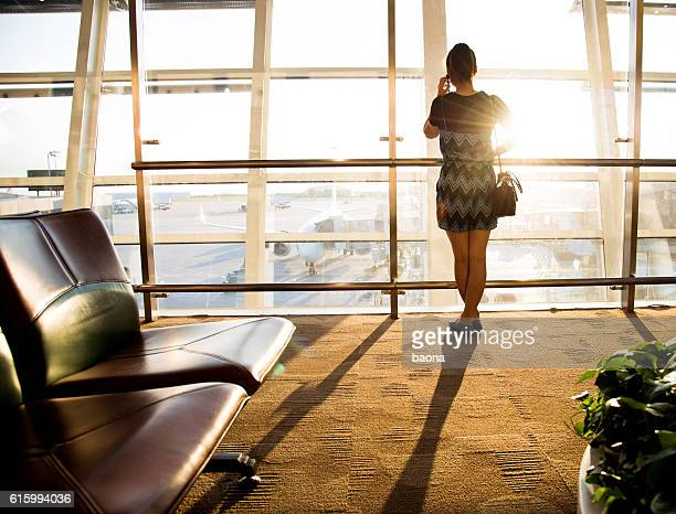 Young woman talking on mobile phone at airport