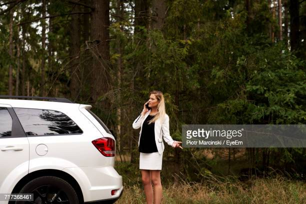 Young Woman Talking On Mobile Phone By Broken Down Car