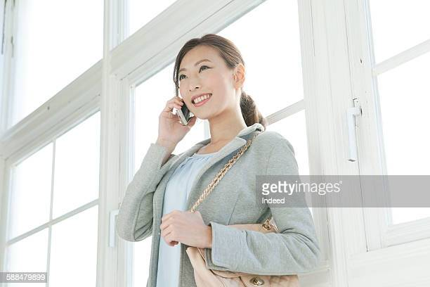 Young woman talking on mobile phone by window