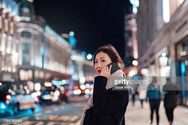young woman talking on mobile phone on the city street at night - motion stock pictures, royalty-free photos & images