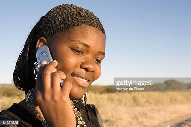 young woman talking on mobile phone, opuwo, kaokoland, namibia - opuwo tribe stock photos and pictures