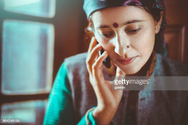 young woman talking on mobile phone. - bindi stock pictures, royalty-free photos & images