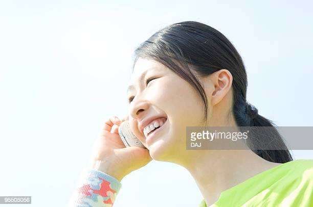 young woman talking on mobile phone - ポニーテール ストックフォトと画像