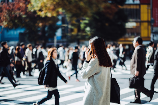 Young woman talking on mobile phone while crossing street in downtown district, against busy commuters and city buildings - gettyimageskorea