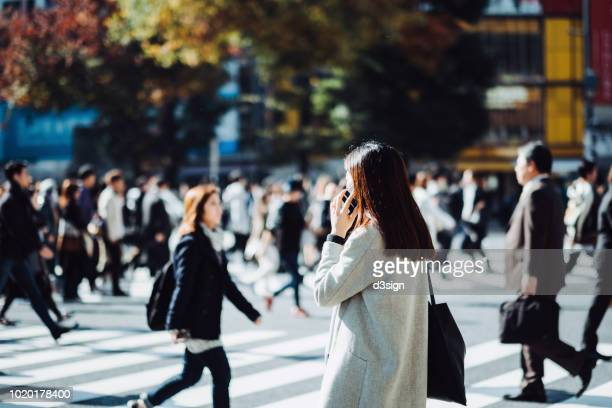 young woman talking on mobile phone while crossing street in downtown district, against busy commuters and city buildings - rush hour stock pictures, royalty-free photos & images
