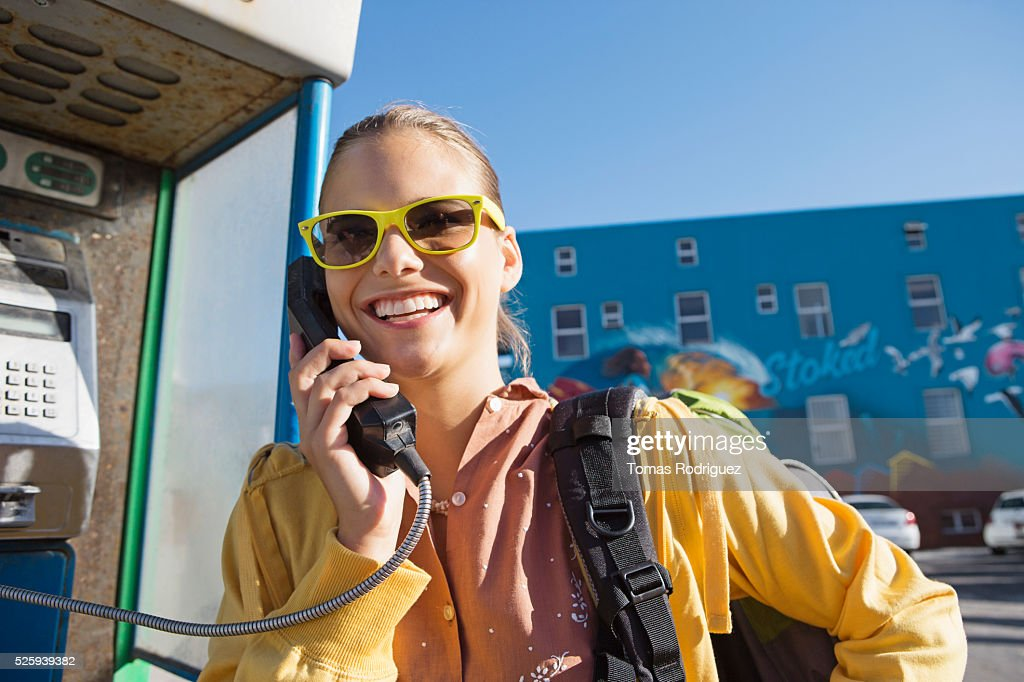 Young woman talking on payphone : Stock Photo