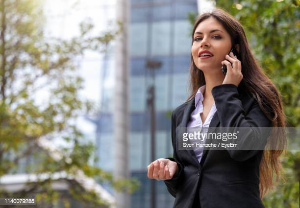 young woman talking on phone against building and tree - businesswoman stock pictures, royalty-free photos & images
