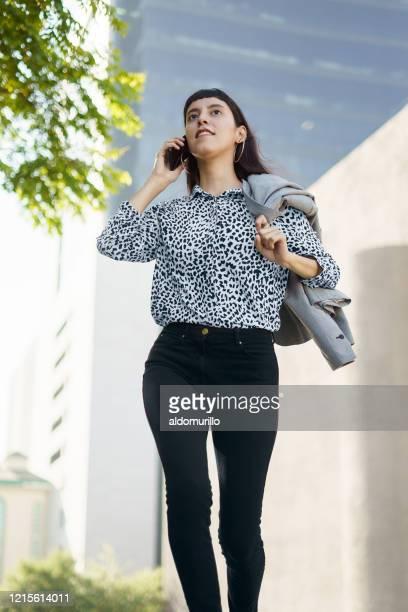 若い女性が電話で話し、速く歩く - メキシコ北部 ストックフォトと画像
