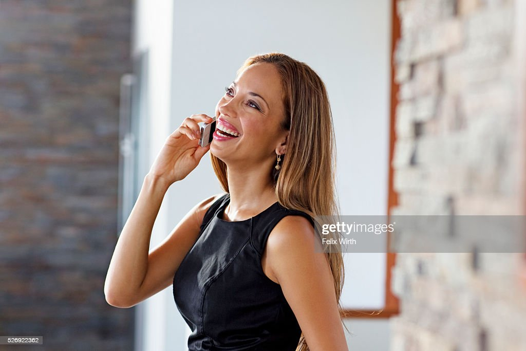 Young woman talking on phone at home : ストックフォト