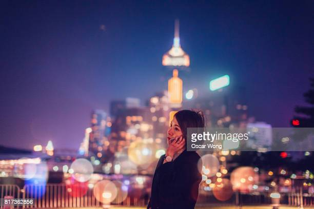 Young woman talking on phone at night against cityscape