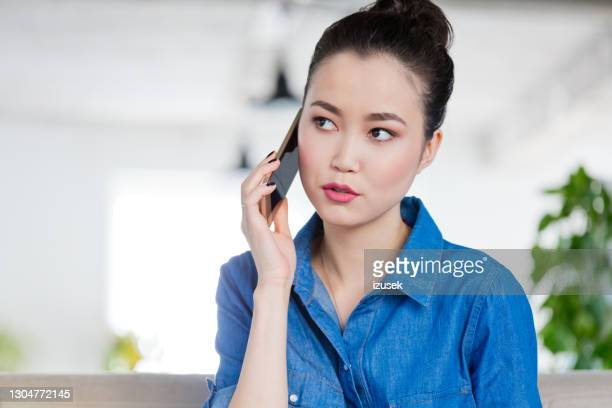 joven hablando por teléfono en lugar de trabajo creativo - izusek fotografías e imágenes de stock