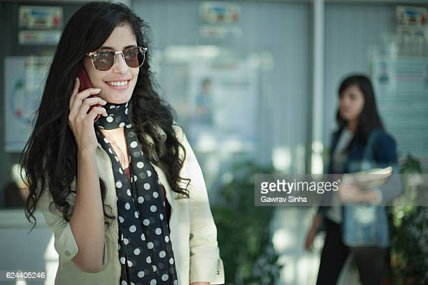 Young woman talking on phone in lobby of office.