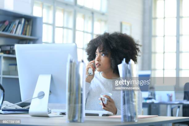 Young woman talking on phone in modern workplace