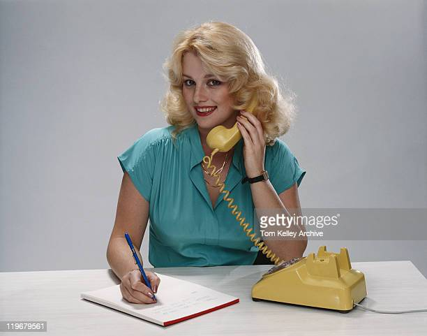Young woman talking on phone, smiling, portrait