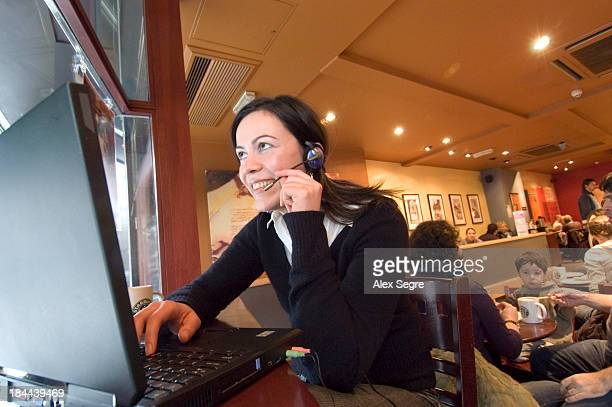 Young woman talking on Skype using WiFi hotspot in Internet cafe, Starbucks coffee shop