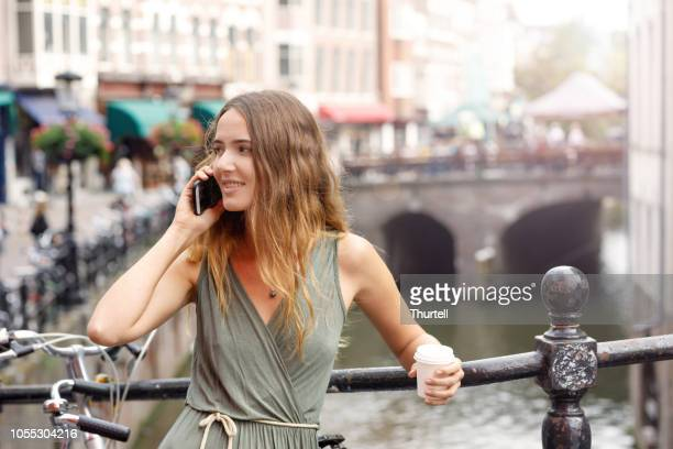 young woman talking on smart phone looking for friends - utrecht stock pictures, royalty-free photos & images