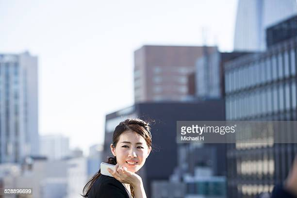 young woman talking on smartphone on rooftop