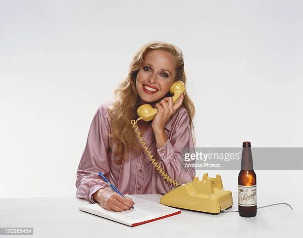 Young woman talking on telephone and beer bottle beside, portrait
