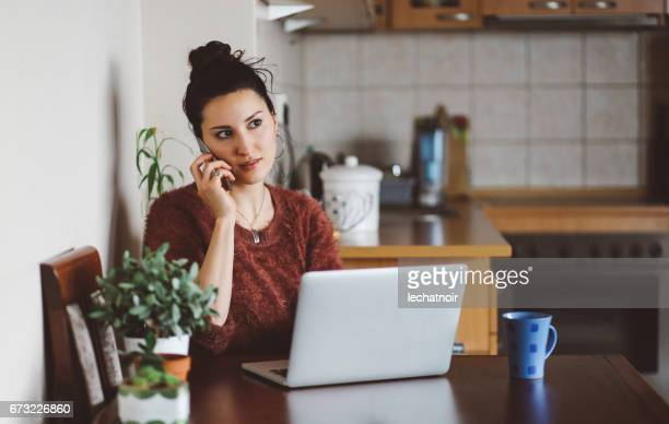 Young woman talking on the cellphone at home