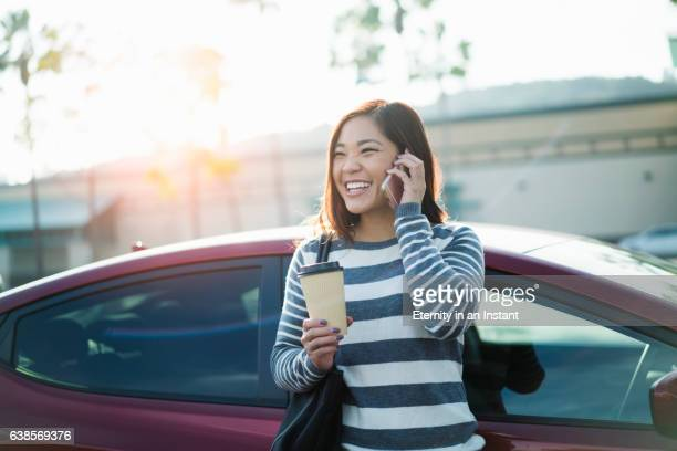 young woman talking on the phone and holding a coffee cup. - east asian ethnicity stock pictures, royalty-free photos & images