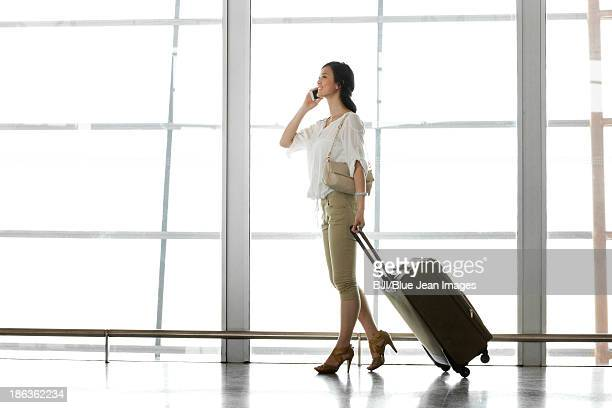 Young woman talking on the phone at the airport