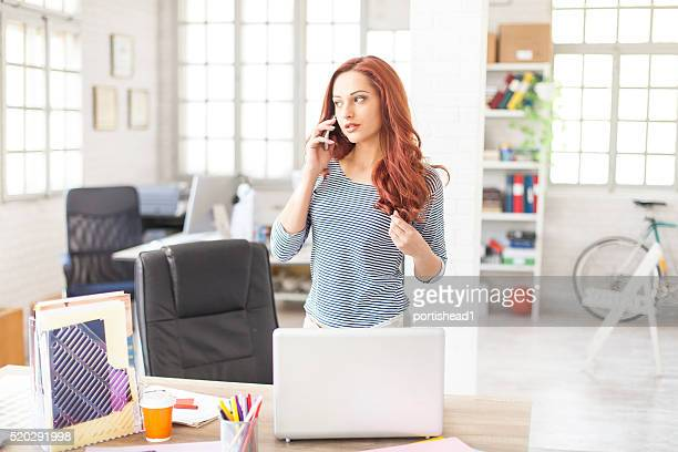 Young woman talking on the phone at workplace