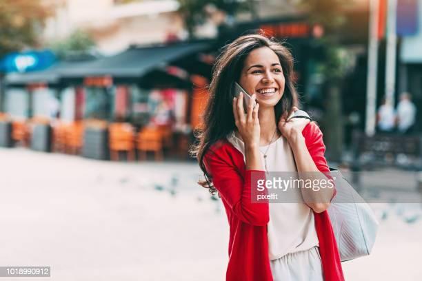 jeune femme parlant sur le téléphone - sac à main rouge photos et images de collection