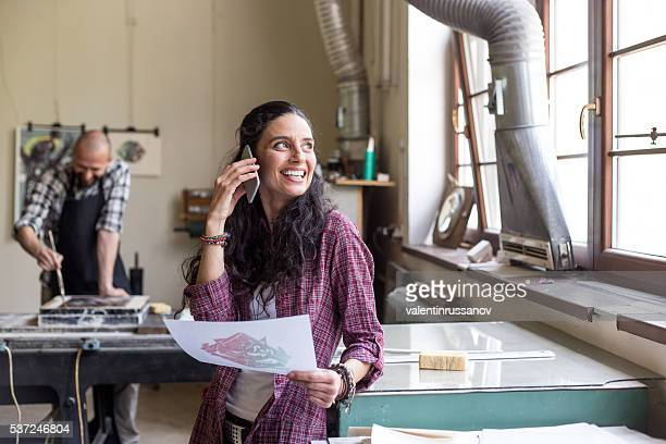 Young woman talking on the phone while printing new texture