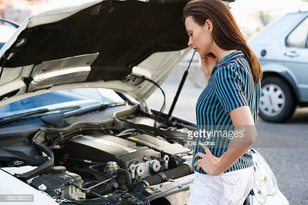 Young woman talking over phone and standing by the broken car