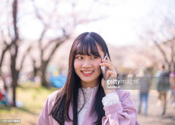 桜の花の下で電話で話している若い女性 - 待つ ストックフォトと画像
