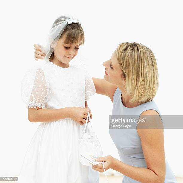 Young woman talking to a girl (11-13) wearing her first holy communion dress
