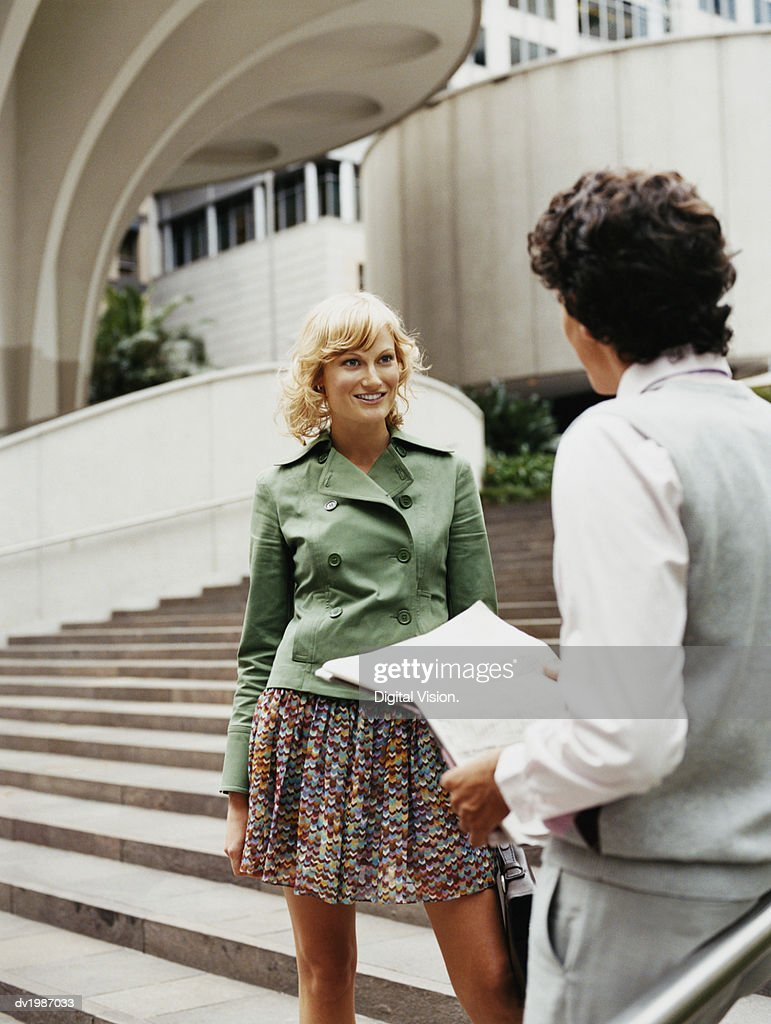 Young Woman Talking to a Man Standing on Steps by a Building in the City : Stock Photo