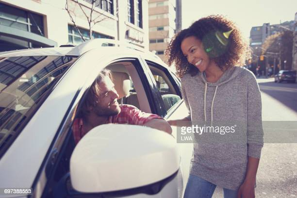 Young woman talking to man in car