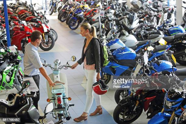 Young woman talking to salesman in motorbike showroom