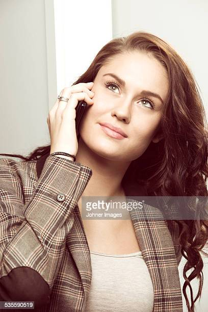 young woman talking via cell phone - brown jacket stock pictures, royalty-free photos & images