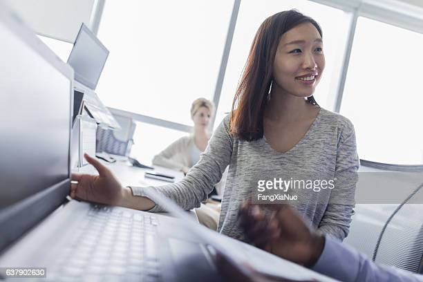 Young woman talking with colleague in technology department